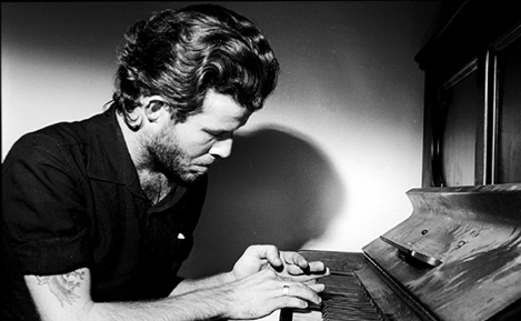 """This 1977 photo shows Tom Waits playing piano in his Tropicana room. Waits supposedly """"enlarged"""" the doorframe in order to get the piano inside. (Photo by Mitchell Rose)"""