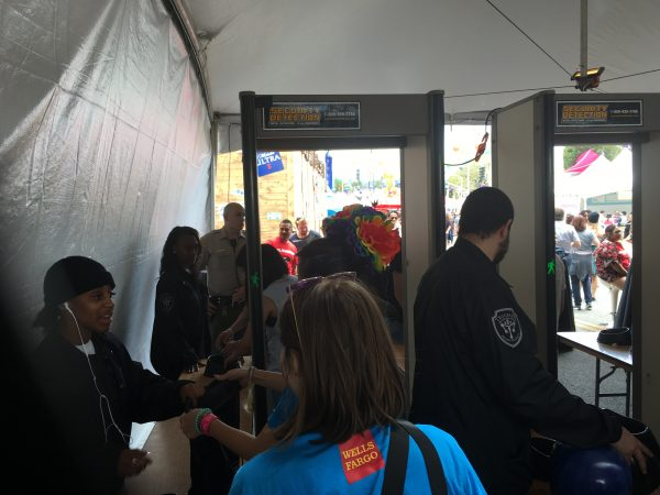 LA Pride festival attendees go through a screening device and have bags and purses checked.