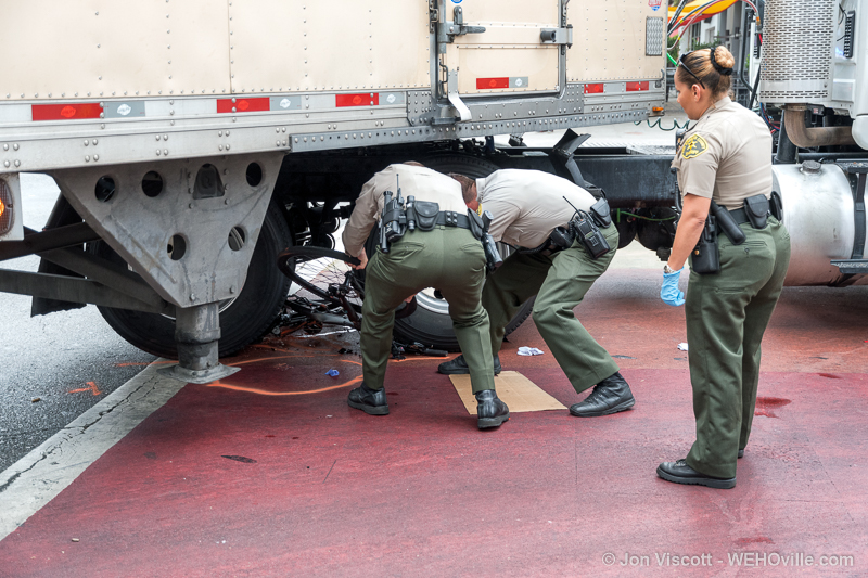 Deputies remove bicycle from under truck. (Photo by Jon Viscott)